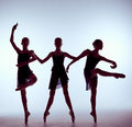 Composition from silhouettes of three young ballet dancers in poses on a gray background the outline shooting girls Stock Photos