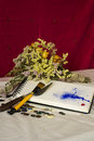 Composition of a sketchbook withered flowers buttons brush spatula and paint an artistic acrylic blue red red background still Royalty Free Stock Photography