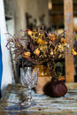 Composition of a vase filled with withered flowers pomegranate and a glass an artistic still life Stock Images