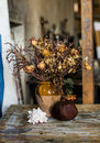 Composition of a vase filled with withered flowers rapana and a pomegranate an artistic still life Stock Photos