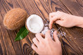 A composition of a whole and cut in a half coconuts with green leaves and man`s hands collect nut flakes. Hawaiian coconuts. Royalty Free Stock Photo