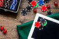 Compulsive gambling. Poker chips and the dice nearby tablet on wooden table top view