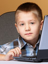 Computer addiction child boy laptop computer brown background Royalty Free Stock Images