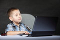Computer addiction child with laptop notebook boy black background Royalty Free Stock Photo