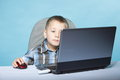 Computer addiction child with laptop notebook boy blue background Royalty Free Stock Photos