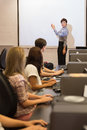 Computer class looking at teacher pointing on projection screen in college Royalty Free Stock Images
