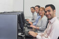 Computer class sitting in front of computers Royalty Free Stock Photo