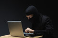 Computer criminal stealing information or hacker in a balaclava sitting at a desk in the darkness off a laptop and Stock Photo