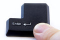 Computer enter key with finger pressing button Royalty Free Stock Photo