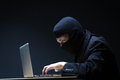 Computer hacker in a balaclava working in the darkness stealing data and personal identity information off a laptop Stock Photo