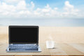 Computer laptop with black screen and hot coffee cup on wooden table top on blurred beach background Royalty Free Stock Photo