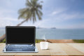 Computer laptop with black screen and hot coffee cup on wooden table top on blurred beach with coconut tree background Royalty Free Stock Photo