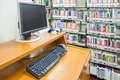 computer in a library with many books and shelves in the background Royalty Free Stock Photo