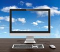 Computer monitor keyboard mouse desk cloudy sky background Royalty Free Stock Image
