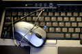 Computer mouse with glasses on keyboard laptop Royalty Free Stock Image