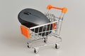 Computer mouse in supermarket pushcart on gray background Stock Image