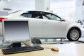 Computer stands on table and new white car in office of shop selling cars Stock Photos
