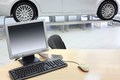 Computer stands on wooden desk and new car stands in office of shop Stock Photo