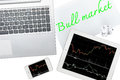 Computer, tablet, smartphone and paper with text bull market is Royalty Free Stock Photo