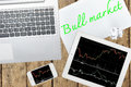 Computer, tablet, smartphone and paper with text bull market on Royalty Free Stock Photo