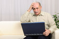 Computer virus old man problem elder looking at laptop display shocked or bad news browsing internet Stock Image