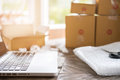 computer at workplace of start up, small business owner, freelance, entrepreneur, SME seller. cardboard parcel box of product for Royalty Free Stock Photo