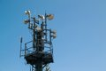 Comunication tower with multiple antennas and blue sky in background Royalty Free Stock Image