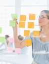 Concentrated artist looking at colorful sticky notes female the office Stock Photos