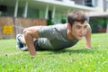 Concentrated athlete fitness man exercising push ups in the park Royalty Free Stock Photography