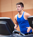 Concentrated athletic man training on a treadmill Stock Photos