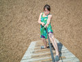 Concentrated beautiful little girl climbing on wooden stairs at kids play ground Royalty Free Stock Photo