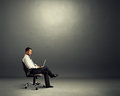 Concentrated businessman sitting in dark room young empty and working with laptop Royalty Free Stock Photography