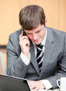 Concentrated businessman using laptop and phoning Royalty Free Stock Photo