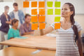 Concentrated businesswoman pointing post its on the wall Royalty Free Stock Photo