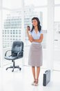 Concentrated businesswoman typing on her mobile phone in office Stock Images