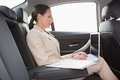 Concentrated businesswoman working in the back seat her car Royalty Free Stock Photography