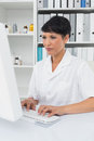 Concentrated female doctor using computer at medical office Royalty Free Stock Image
