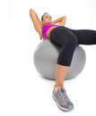 Concentrated fitness young woman doing abdominal crunch on fitness ball Stock Photos