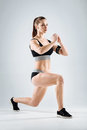 Concentrated girl doing lunges on a grey background Royalty Free Stock Photo
