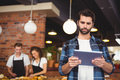 Concentrated hipster using tablet in front of working barista
