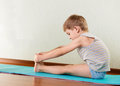 Concentrated little boy exercising stretching gym Royalty Free Stock Image