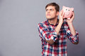 Concentrated man in checkered shirt holding and shaking piggy bank Royalty Free Stock Photo