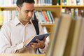 Concentrated mature student using tablet pc in library against bookshelf the Royalty Free Stock Photography
