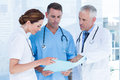 Concentrated medical colleagues analyzing file together in the hospital Royalty Free Stock Images