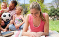 Concentrated mother reading at a picnic Royalty Free Stock Images