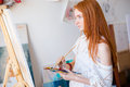 Concentrated pensive woman painter with long hair painting on canvas young red using oil paints in art studio Stock Photos
