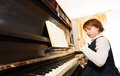 Concentrated small girl in uniform playing piano beautiful school the with notes during lesson indoors Royalty Free Stock Image