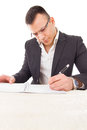 Concentrated thoughtful professor writing evaluation and adding with glasses reviews Stock Photography