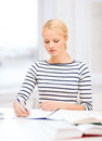 Concentrated woman studying in college education school and business concept with books and notebook Stock Photography