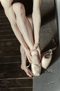 Concentrated woman wearing her ballet shoes in the studio